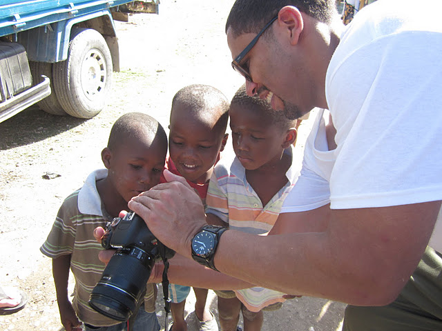 Kids everywhere LOVED cameras. Adimu with our group shows them his pics.